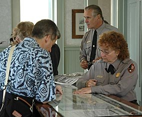 Two rangers provide information to two visitors at an information desk