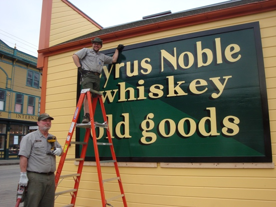 Two NPS staff hanging sign on historic building