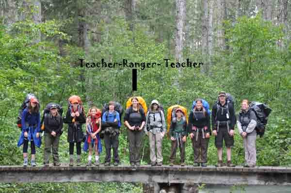 "People stand in a line on a wooden bridge wearing backpacking gear in a natural setting.  Text above middle person says ""Teacher-Ranger-Teacher"""