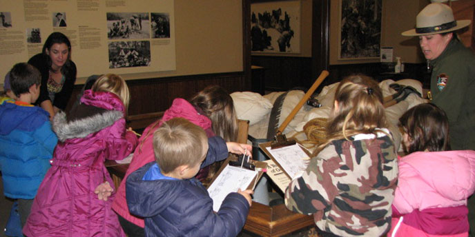 Children with clipboard stand with a ranger in a museum.