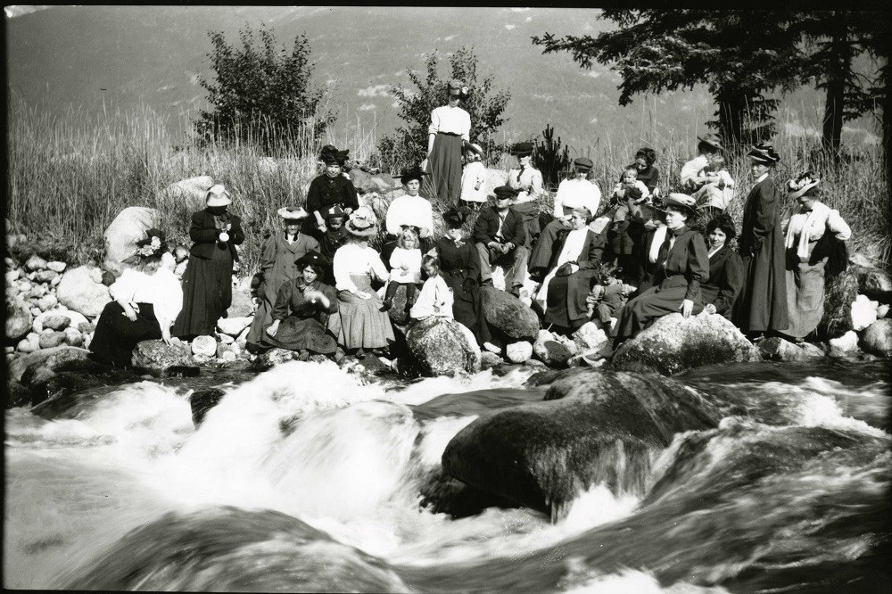 Black and white photo of women and children sitting by a flowing river in a natural setting.
