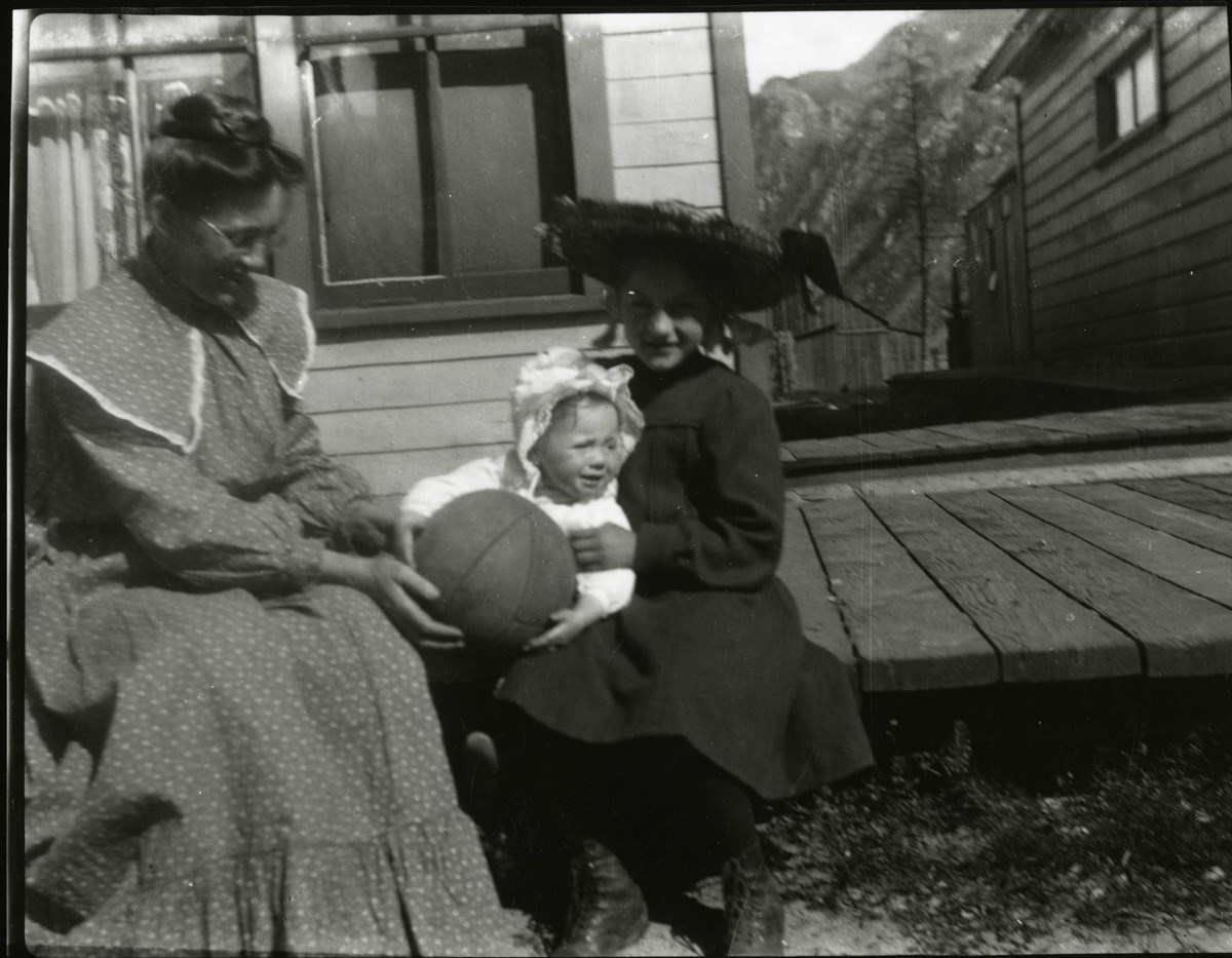 Black and white photo of two women sitting on a wooden platform playing with a baby who is holding a basketball.