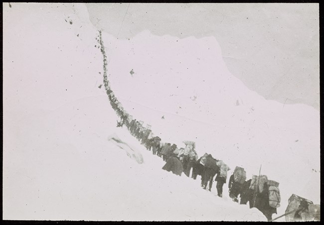 Black and white photo of line of people climbing a steep, snowy slope