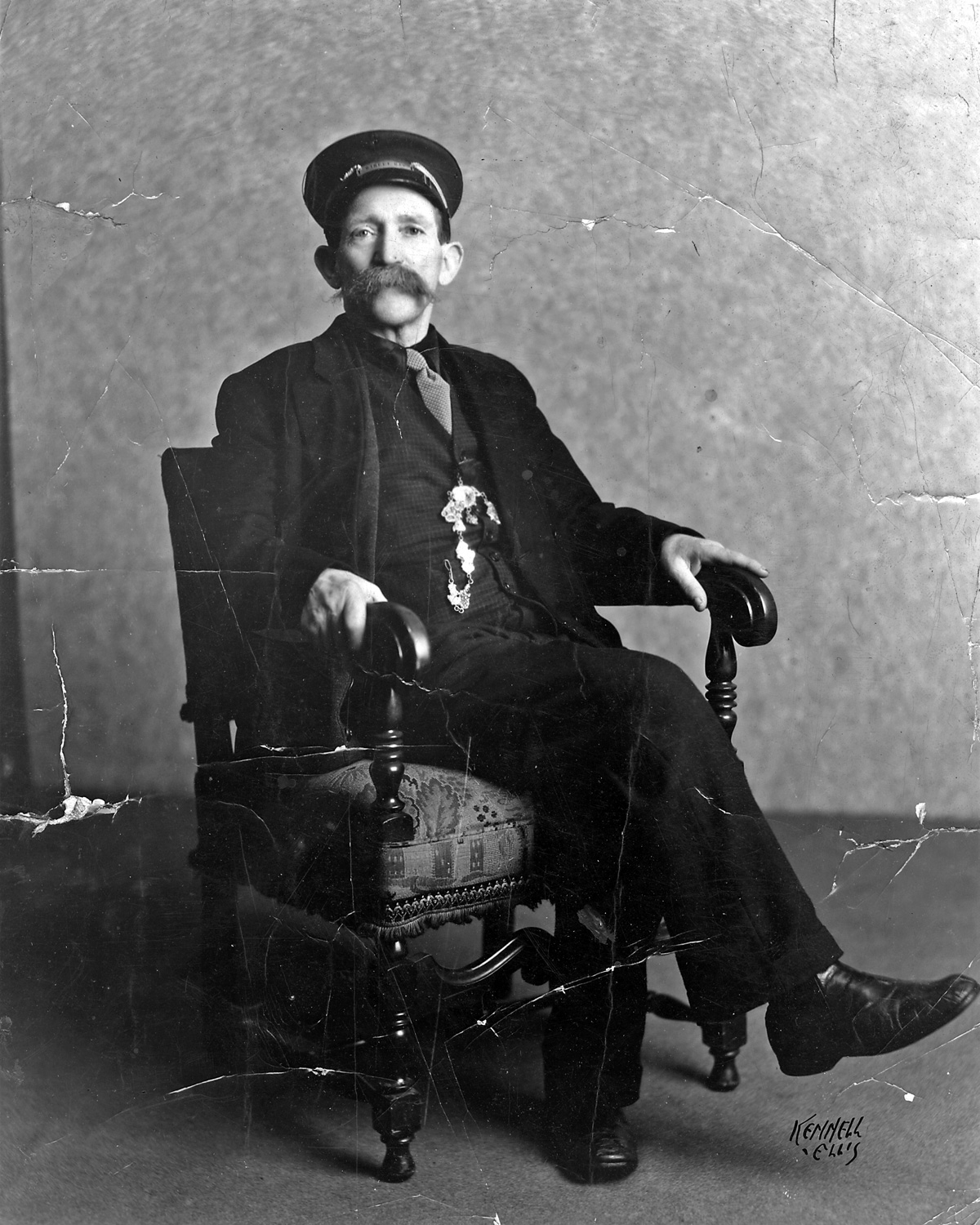 Black and white historic portrait photo of a man seated in a chair
