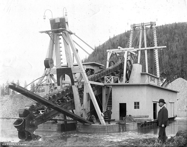 A large gold dredge with a man in a bowler hat in front of the many dredge buckets.