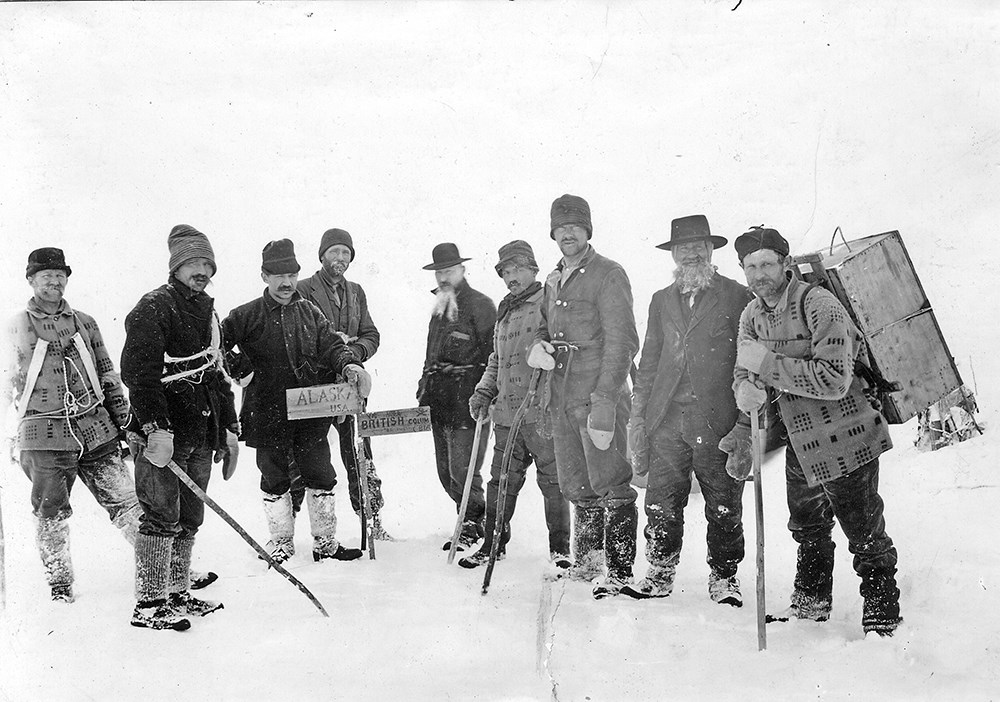 Nine men stand at the Alaska British Columbia border in the snow