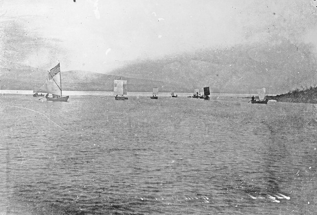 Black and white photo of boats with sails on a large body of water