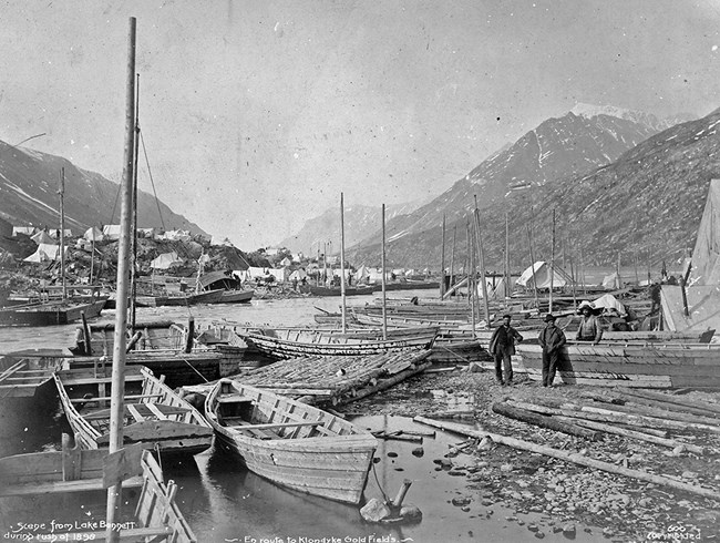 Black and white photo of rough wooden boats stretching from foreground to background. Two men pose midground with mountains and tent city behind them.