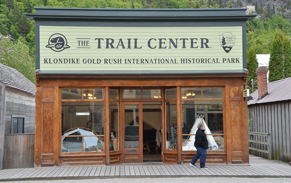 "A building with large windows displaying a modern and historic tent.  A large sign reads ""The Trail Center"" with NPS and Parks Canada logos"