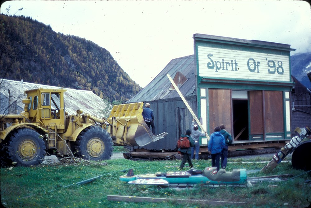 "large machinery approaches a small building with large sign ""Spirit of '98"""