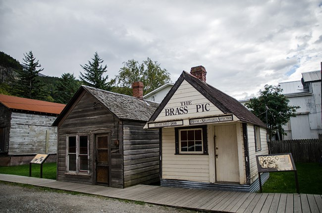 two small buildings with wayside exhibits on either side