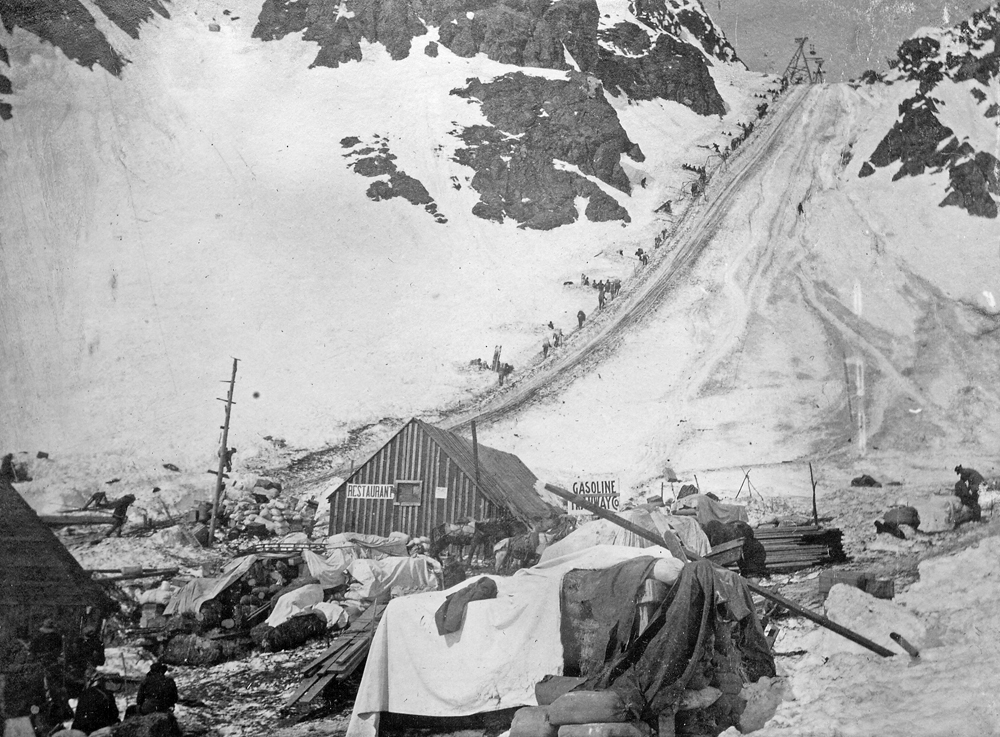 Historic photo of the line of people walking up steep snowy pass with buildings and supplies in foreground