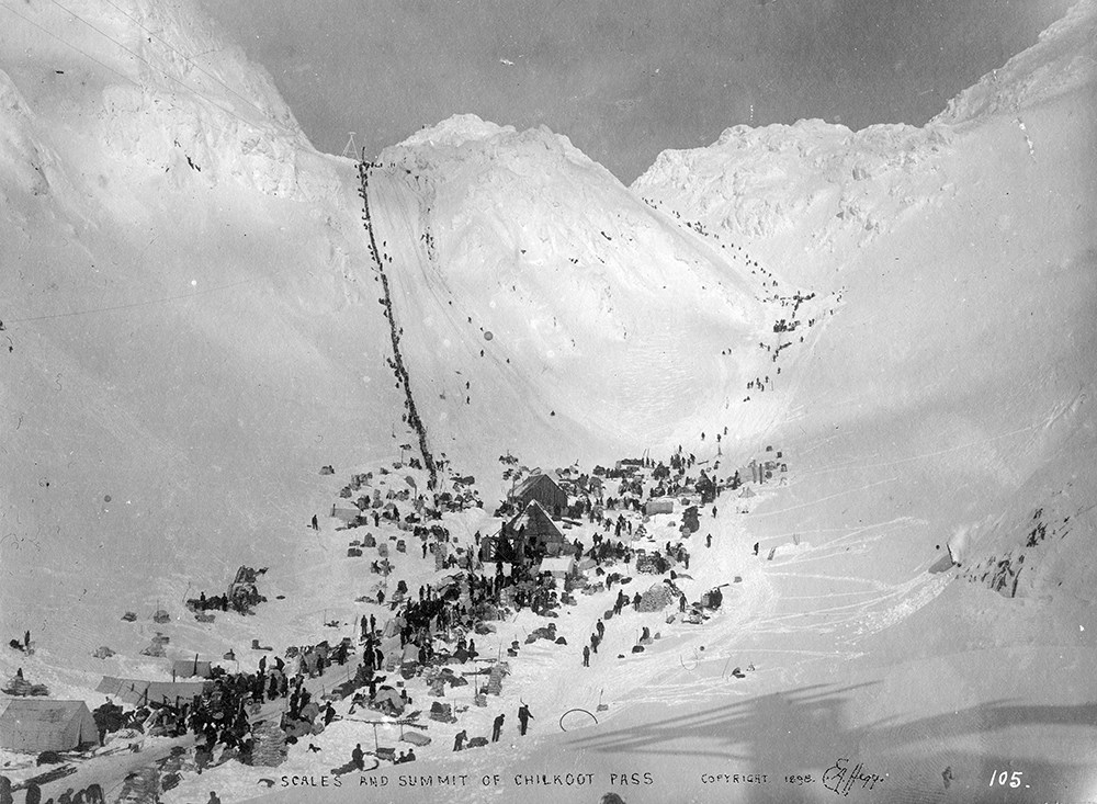 Black and white photo of tents and people collected at the base of two snowy mountain passes.