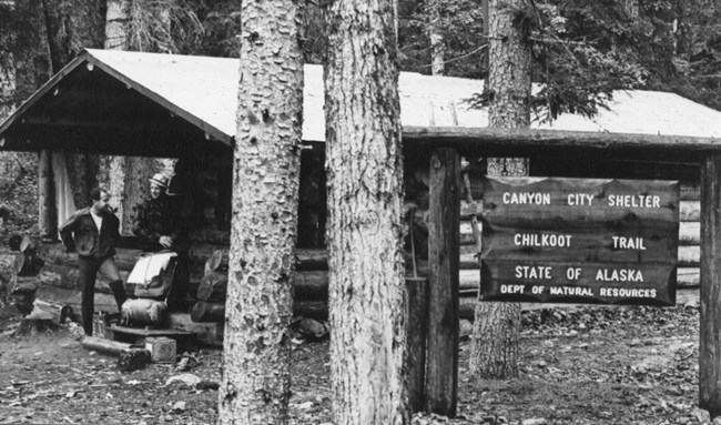 "Black and white photo backpacker standing on porch of log cabin with a sign reading ""Canyon City Shelter Chilkoot Trail State of Alaska Dept of Natural Resources"""