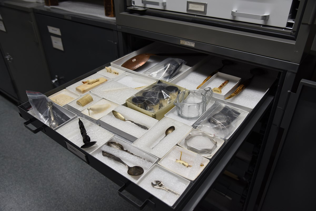 color photo of a wide and shallow grey drawer filled with small open topped white boxes housing various small artifacts