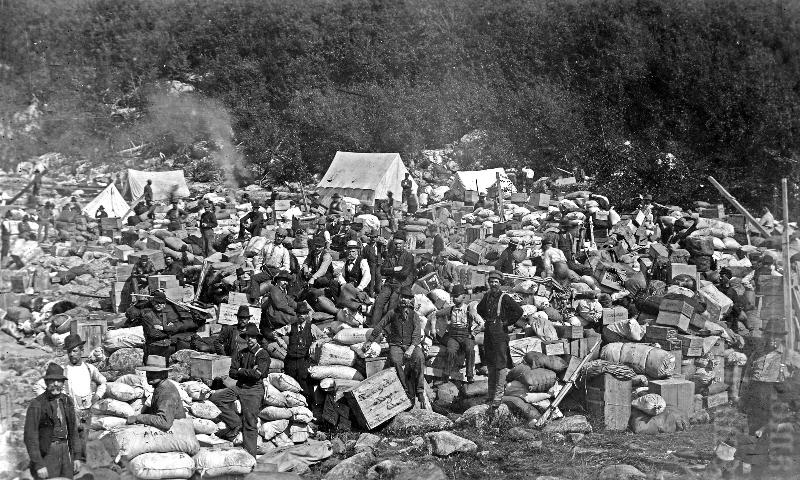 Black and white photo of men posed with piles of boxes and sacks in the foreground and white canvas tents in the back.