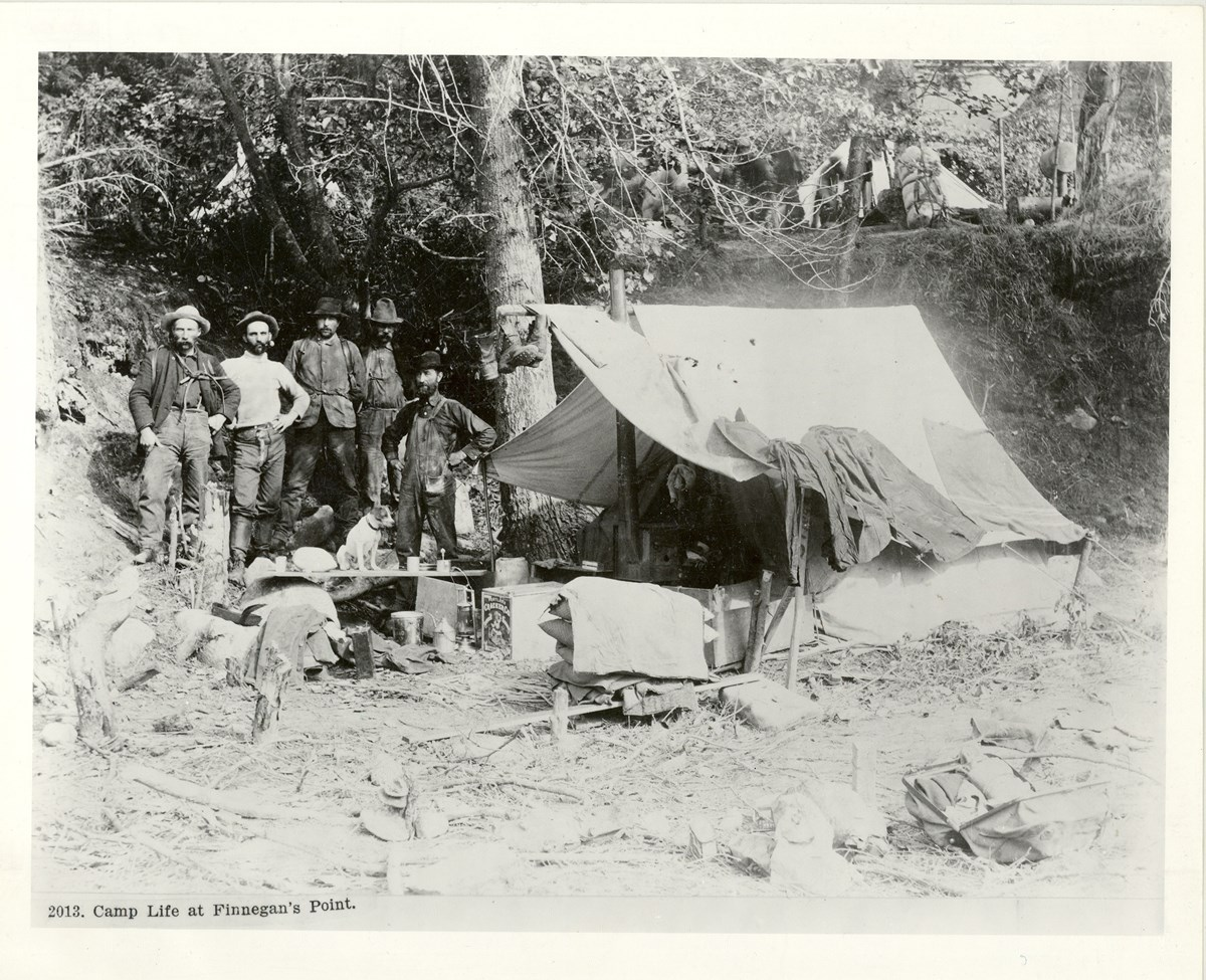 Five men stand with a canvas tent and supplies.