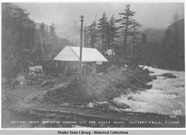 Small cabin, telephone pole, and log bridge next to roaring river in a forested area.