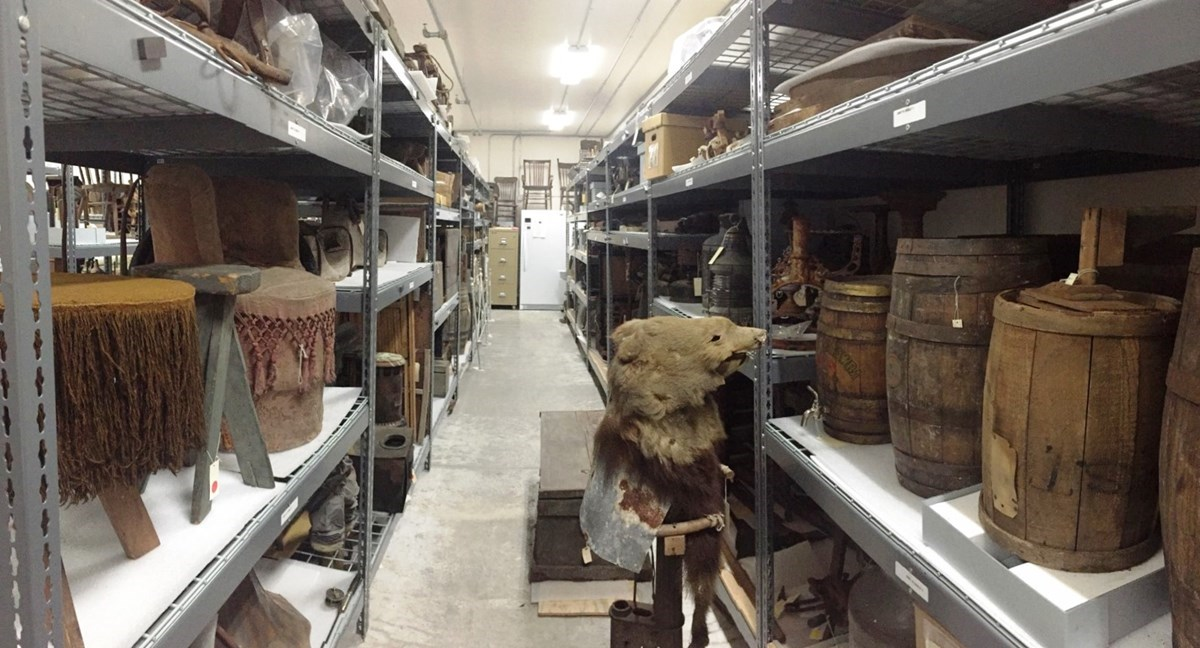 Color photo of a row of gray shelves holding various museum collection artifacts