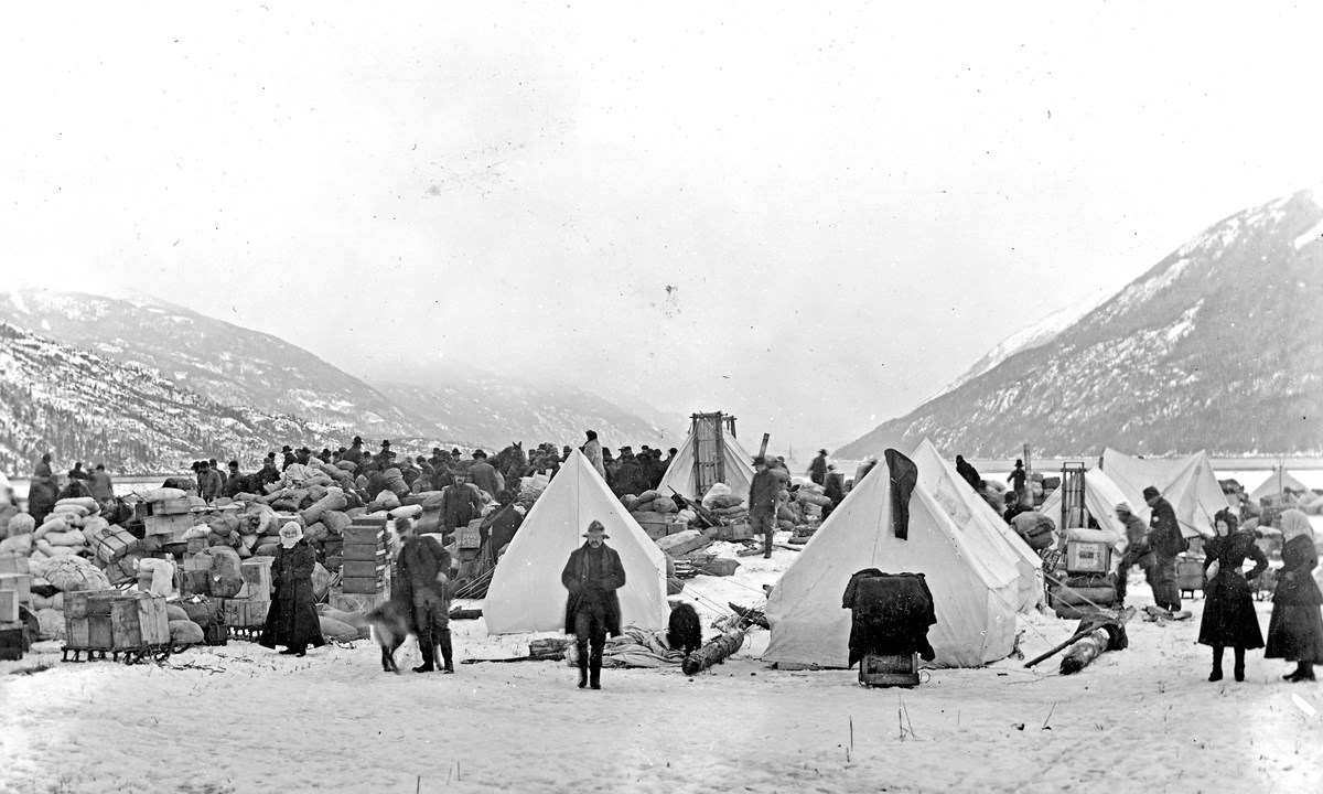 Black and white photo of tents, supplies, and people on a snowy beach