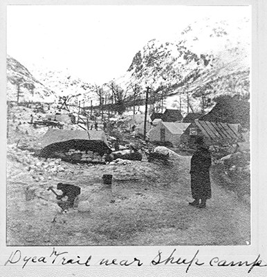 Black and white photo of two people working amid tents and shanties with a snowy mountain backdrop