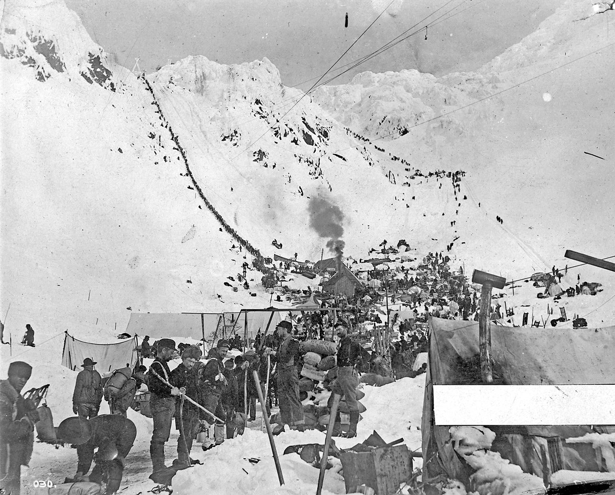 Black and white photo of people and gear and tents gathered at the base of two snowy mountain passes.  Wires cross the sky.