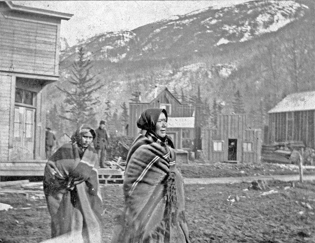 Two Native women wrapped in blankets walk down a muddy street.