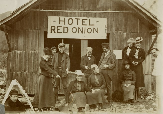"Group of a dozen men and women in old fashioned clothes pose in front of a building with sign ""Hotel Red Onion"" handwritten caption reads ""Canyon City Aug 4th 1901"""
