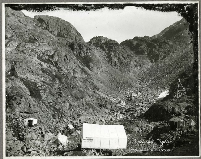Black and white photo of a few tents and buildings in front of rocky mountain backdrop