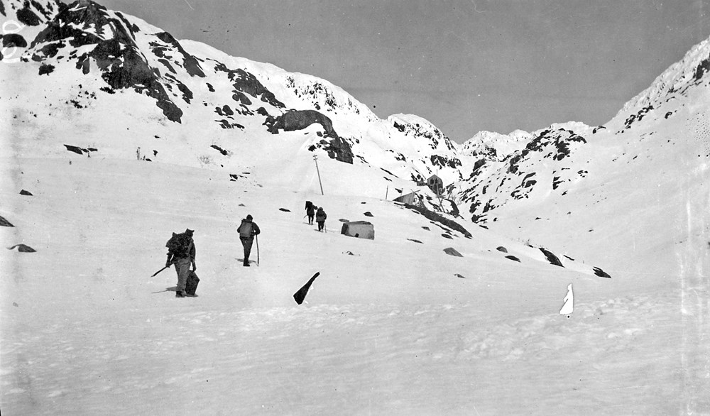 Figures walk up a snowy slope surrounded by snowy mountains.