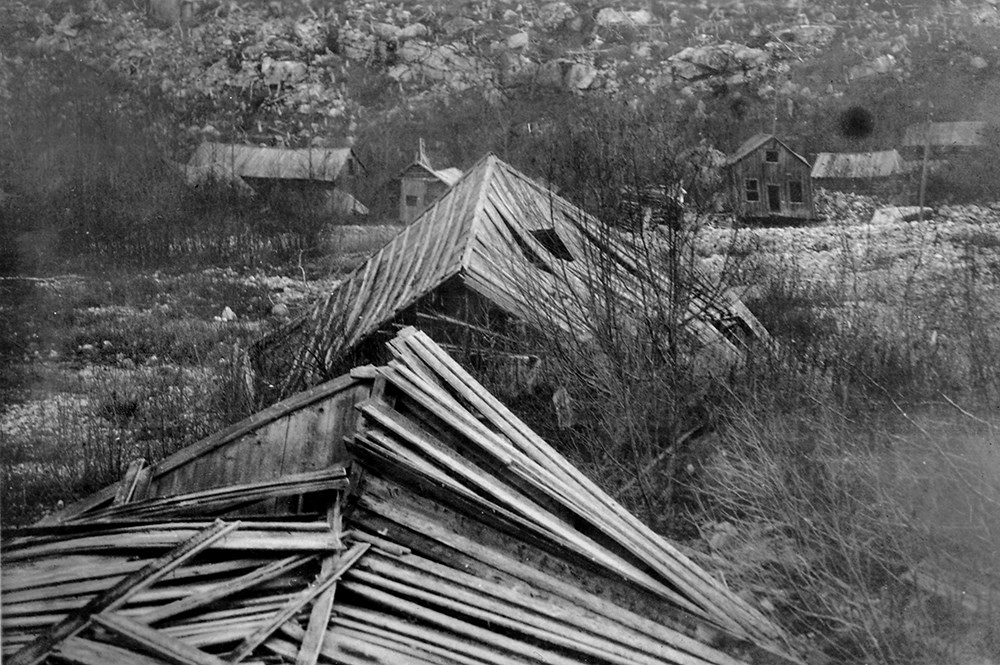 Black and white photo of collapsing buildings in rocky brush area