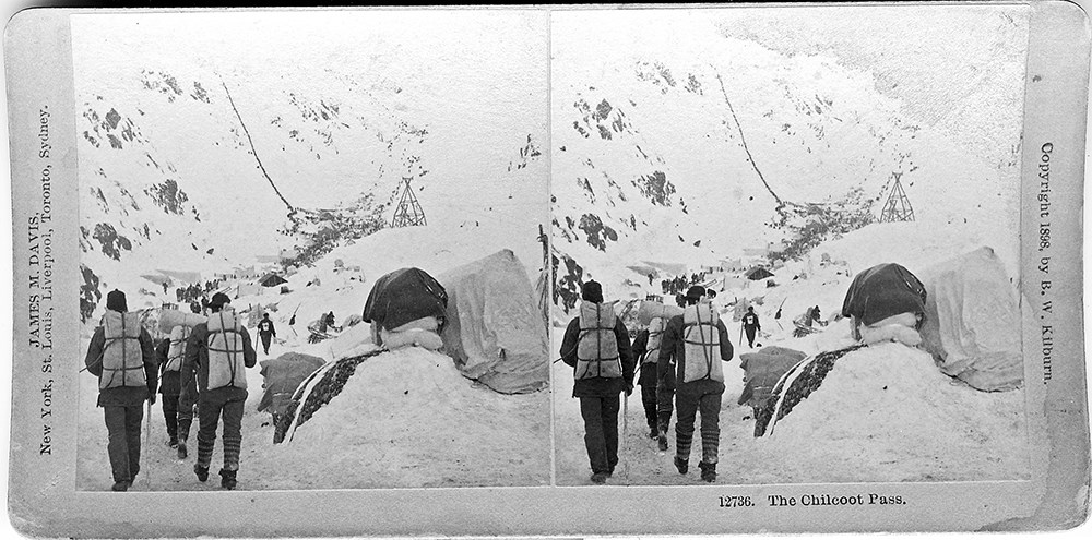 Black and white stereoscope image of hikers with packs walking away from the camera toward a narrow valley with people climbing a snowy pass in background.