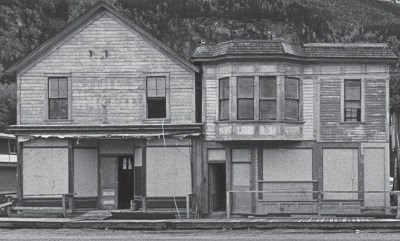 Black and white photo of three unkempt old buildings.