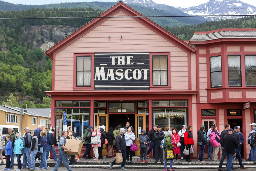 "Brightly colored building with sign ""The Mascot"" and a crowd of people out front"