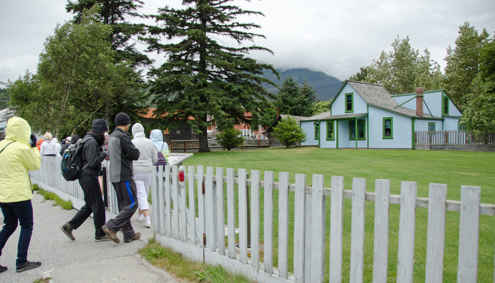 People approach a blue house with a green lawn and picket fence.