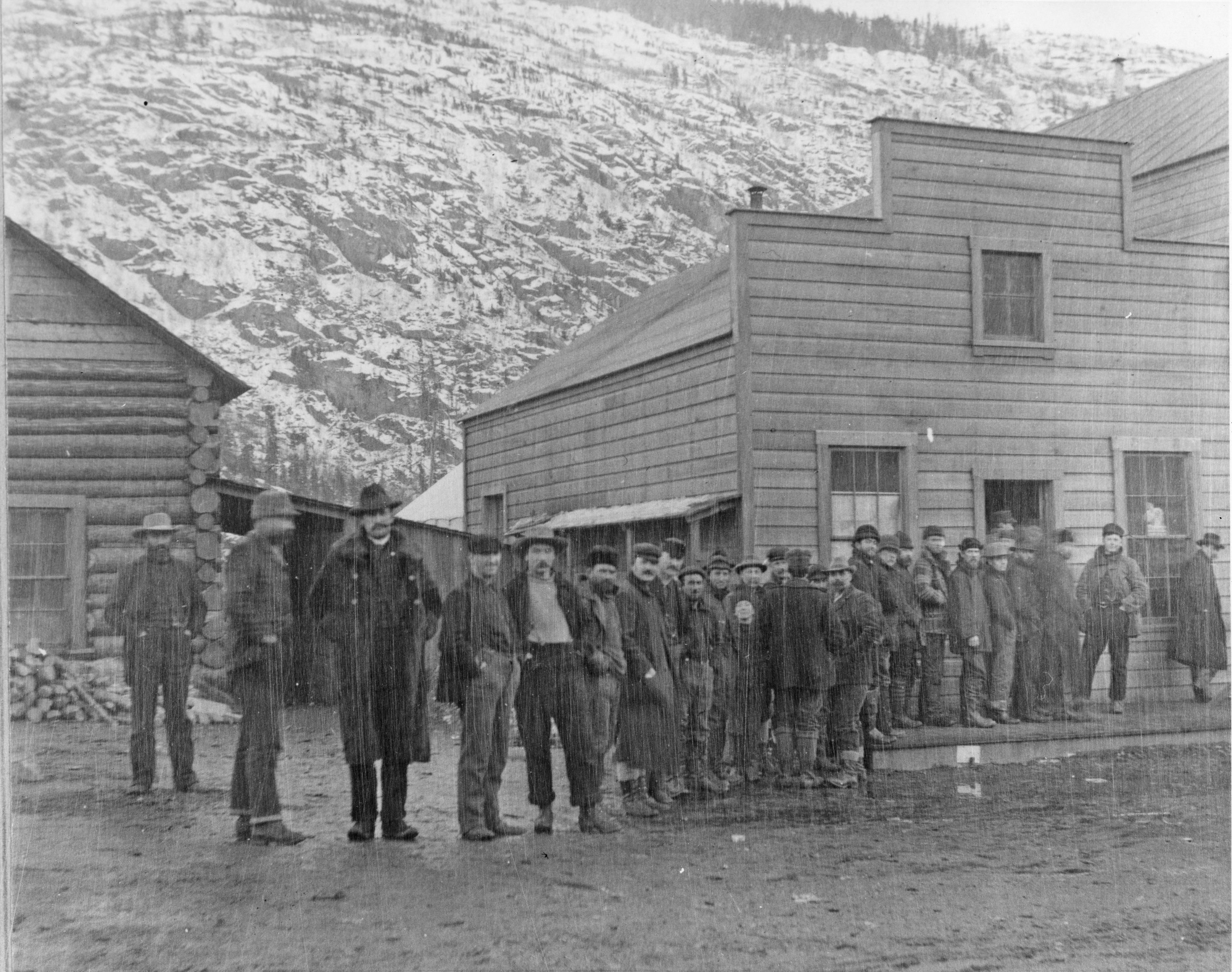 Men stand in a line in front of a wooden building in winter
