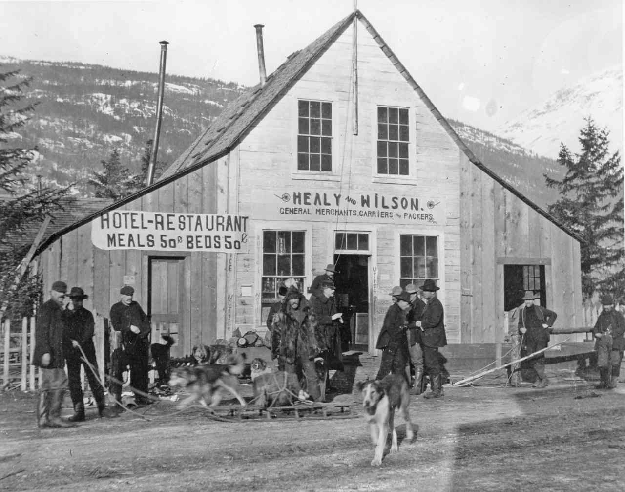 "People stand in front of a wooden building with sign ""Healy & Wilson"""