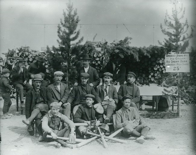 Black and white photo of nine men in three rows with baseball bats arranged in the foreground.
