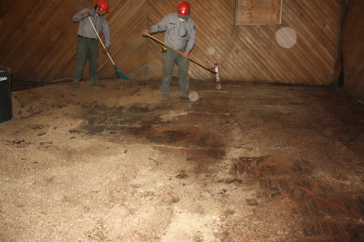 Modern color photograph of two men with a broom and rake clearing the floor of a wooden interior room.