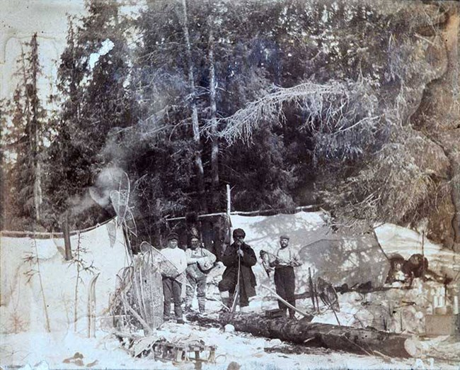People stand in the snow among trees and canvas tents