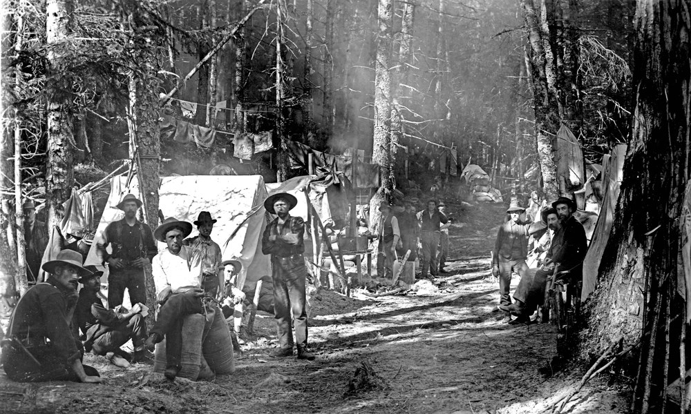 Men sit at a tent camp along a forested trail.