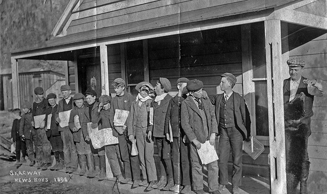 A dozen newsboys stand on a porch holding newspapers