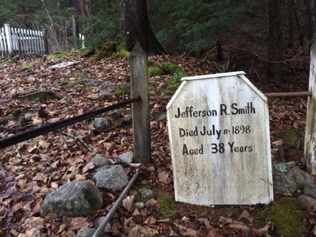 "Wooden grave marker with writing ""Jefferson R. Smith Died July 8 - 1898 Aged 38 Years"" inside a fence with leaves on the ground."