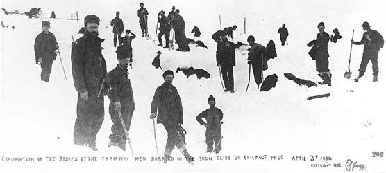 Black and white photo of men holding shovels standing in a snowfield