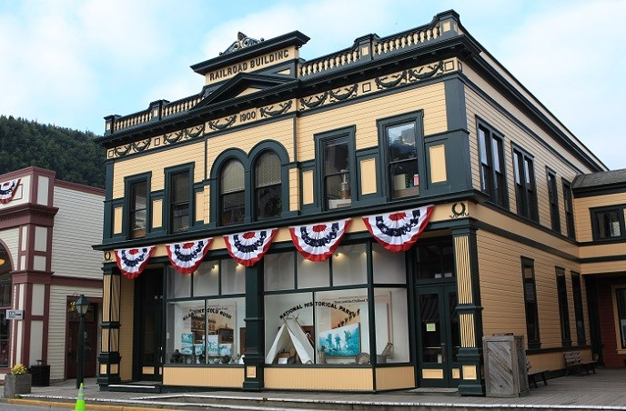 Historic yellow building with green trim decorated with patriotic bunting.