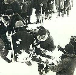 Historic black and white photo of men lifting a frozen body