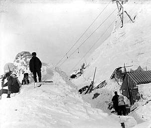 Black and white photo of men standing on deep snowpiles