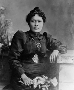 Black and white photograph of Kate Carmack seated holding flowers
