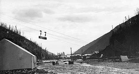 Historic photo of an item on a tram line flying over a rough valley camp.
