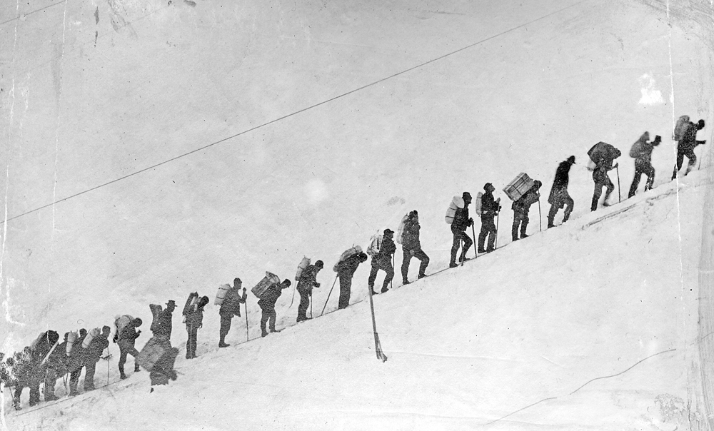 People with gear on their backs stand in a single file line headed uphill with a snowy backdrop.